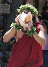 Pili in traditional Hawaiian garb sounding ceremonial conch shell